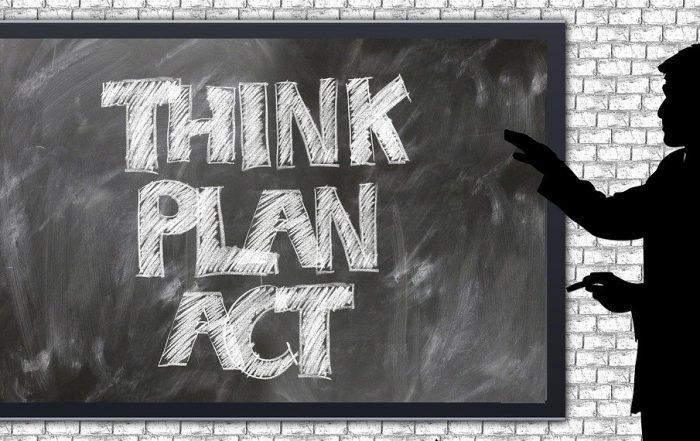 A man is pointing at a black board, representing product manager main activities with the words think, plan, act.