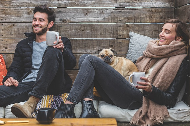 Two people with a dog smileying. This image represents a pleasant meeting between two friends.