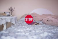 The picture represents a bed and a book on the bed and in front of them there is a stop sign