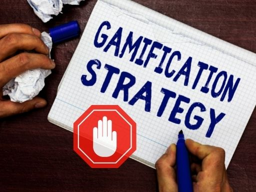 """The picture represents a notepad written on it """"Gamification Strategy"""" and a red sign on top with a hand representing a stop sign."""